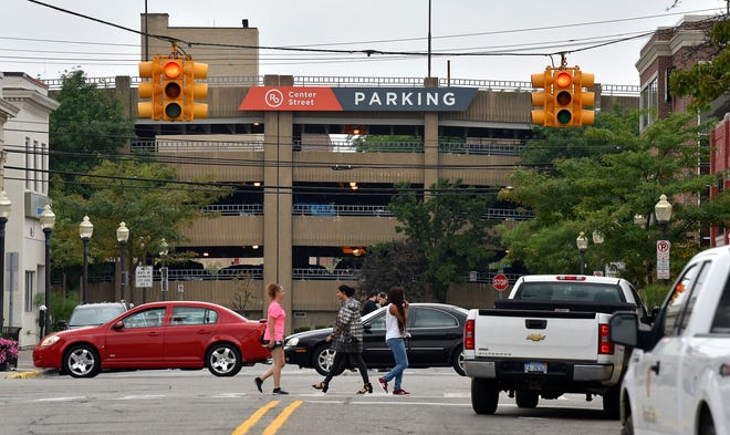 Pedestrians on Main Street cross West Third St. with the Center Street parking deck in the background in Royal Oak.