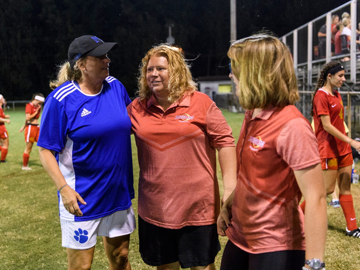 Memorial Head Coach Angie Lensing, left, and Mater Dei Head Coach Amy Weber, center, talk after their teams went head-to-head at the EVSC Soccer Fields in Evansville, Ind., Monday, Aug. 20, 2018. The Tigers defeated the Wildcats 4-0.