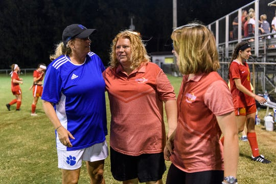 Memorial Head Coach Angie Lensing, left, and Mater Dei Head Coach Amy Weber, center, talk after their teams went head-to-head at the EVSC Soccer Fields in August.
