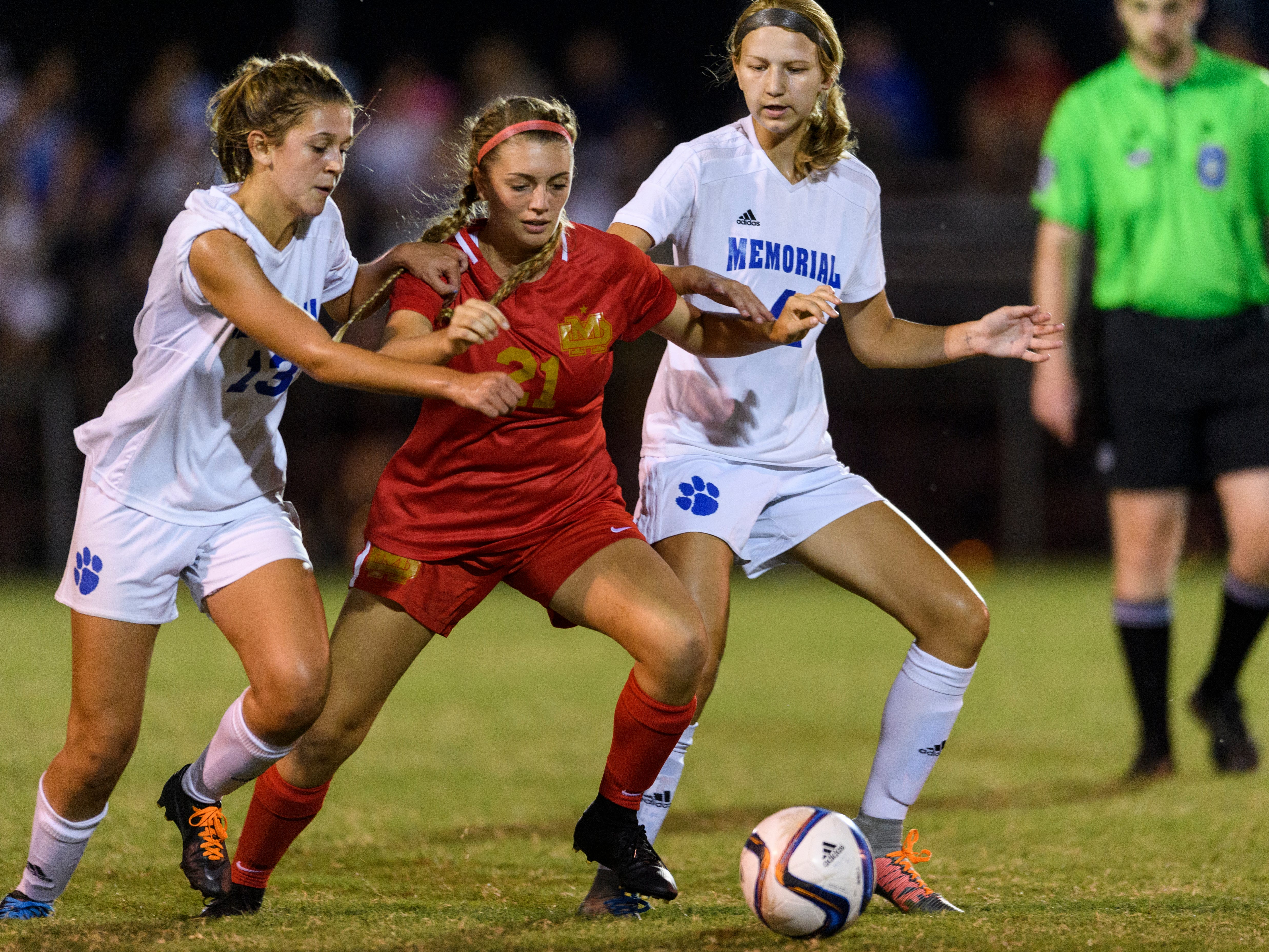Memorial's Eve Timmons (13), Mater Dei's Audrey McDurmon (21) and Memorial's Abby Burger (4) fight for possession of the ball at the EVSC Soccer Fields in Evansville, Ind., Monday, Aug. 20, 2018. The Tigers defeated the Wildcats 4-0.