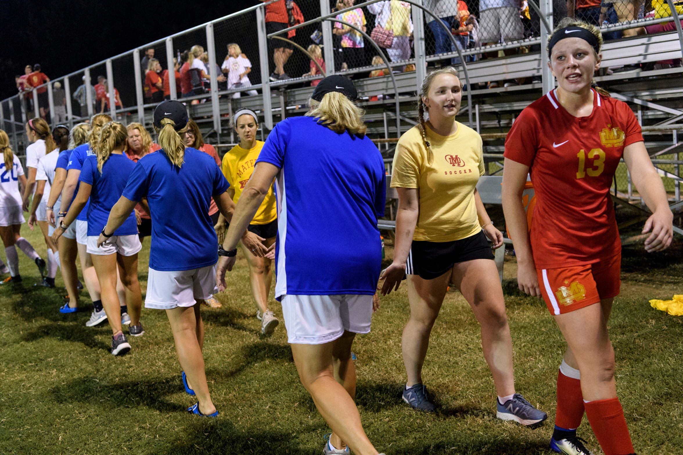 Mater Dei's Katherine Hahn (13), right, and Anna Bury (10), second from right, congratulate the Memorial Tigers after losing 4-0 at the EVSC Soccer Fields in Evansville, Ind., Monday, Aug. 20, 2018.
