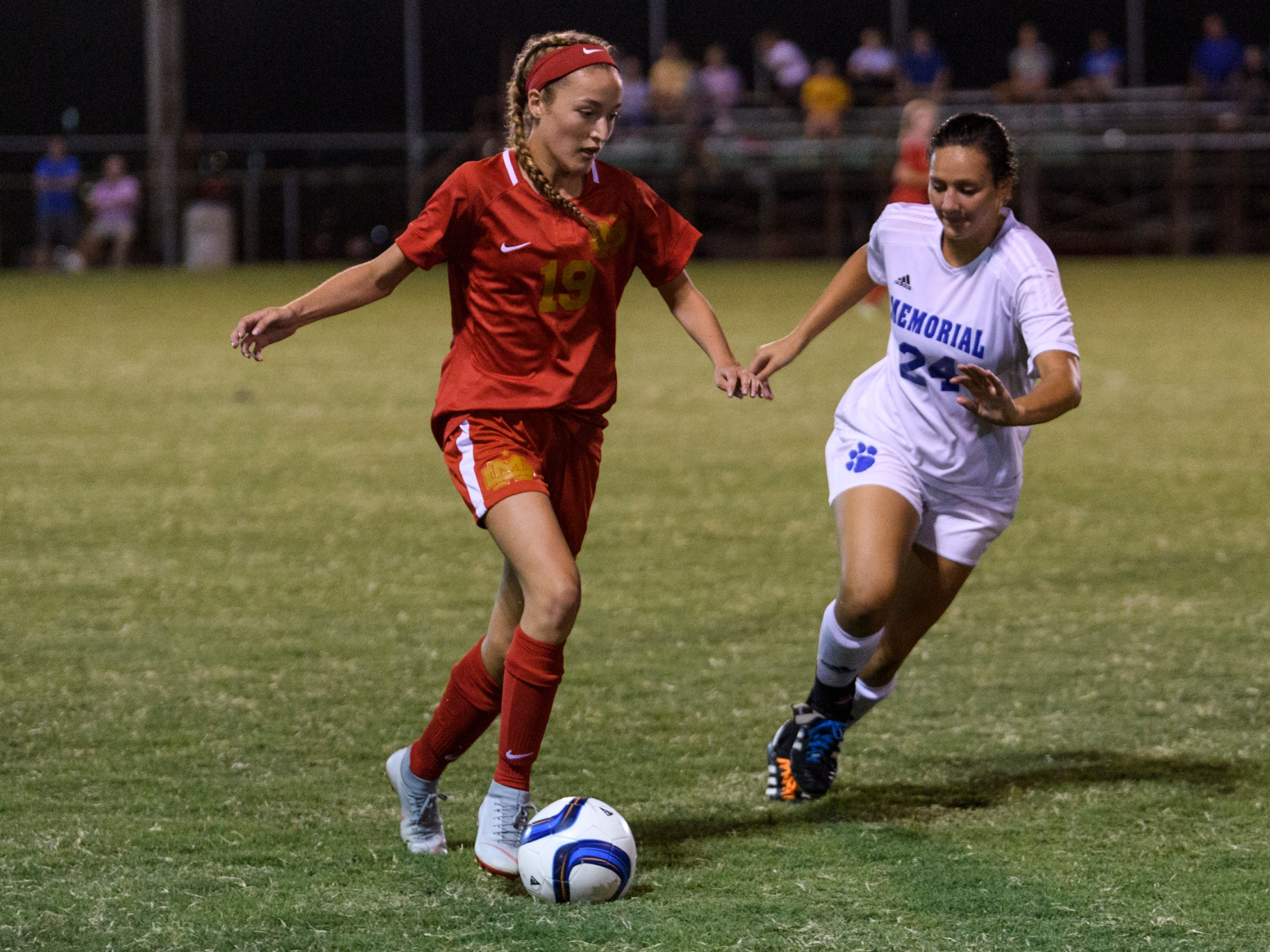 Mater Dei's Miranda Nosko (19) drives the ball down the field as Memorial's Olivia Schitter (24) attempts to make a steal at the EVSC Soccer Fields in Evansville, Ind., Monday, Aug. 20, 2018. The Tigers defeated the Wildcats 4-0.