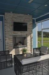 A stone wall on the lanai features a television and fireplace.