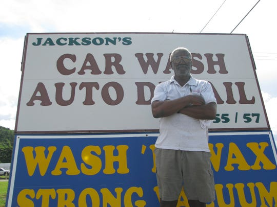 In this Aug. 2009 file photo, Fred Jackson, owner and manager of Jackson's Car Wash and Detail center, stands in front of his company's sign. Jackson died Aug. 7 in Maryland.