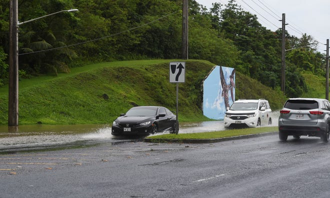 Motorists pass through flooded areas of Piti due to heavy rain on Aug. 21, 2018.