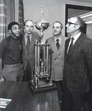 Phil Buck of Madison Heights (right) and  coaches of the other three state final teams look over the state championship trophy at the Assembly Hall in Bloomington (from left are Ivory Brown of Gary West, George Marshall of Jeffersonville, Myron Dickerson of Connersville).