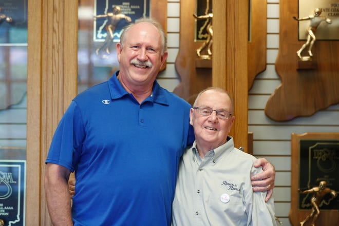 Former Roncalli High School Football Coaches, Bruce Scifres, left, and Bob Tully, right, stand in front of the trophy case they helped fill at the school. The two will be inducted together into the Indiana Football Hall of Fame.