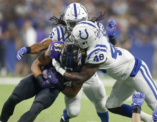 Colts linebacker Skai Moore (48) hits  Ravens wide receiver Willie Snead (83) with the help from Clayton Geathers (26) in the first half of their preseason football game at Lucas Oil Stadium on Monday.