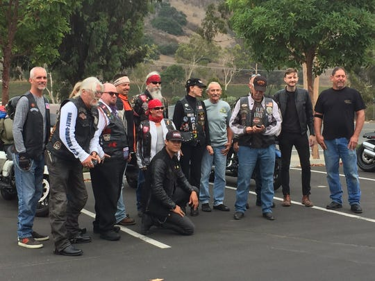 Harley-Davidson riders pose for photographs before heading to Milwaukee.