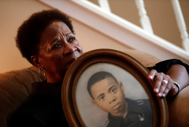 In this Aug. 9, 2018 photo, Eberlene King poses with a photograph of her brother William Roy Prather when he was about 15-years-old at her home in Doraville, Ga. Prather was shot in the face on Halloween night 1959 in Corinth, Miss., and died the next day.