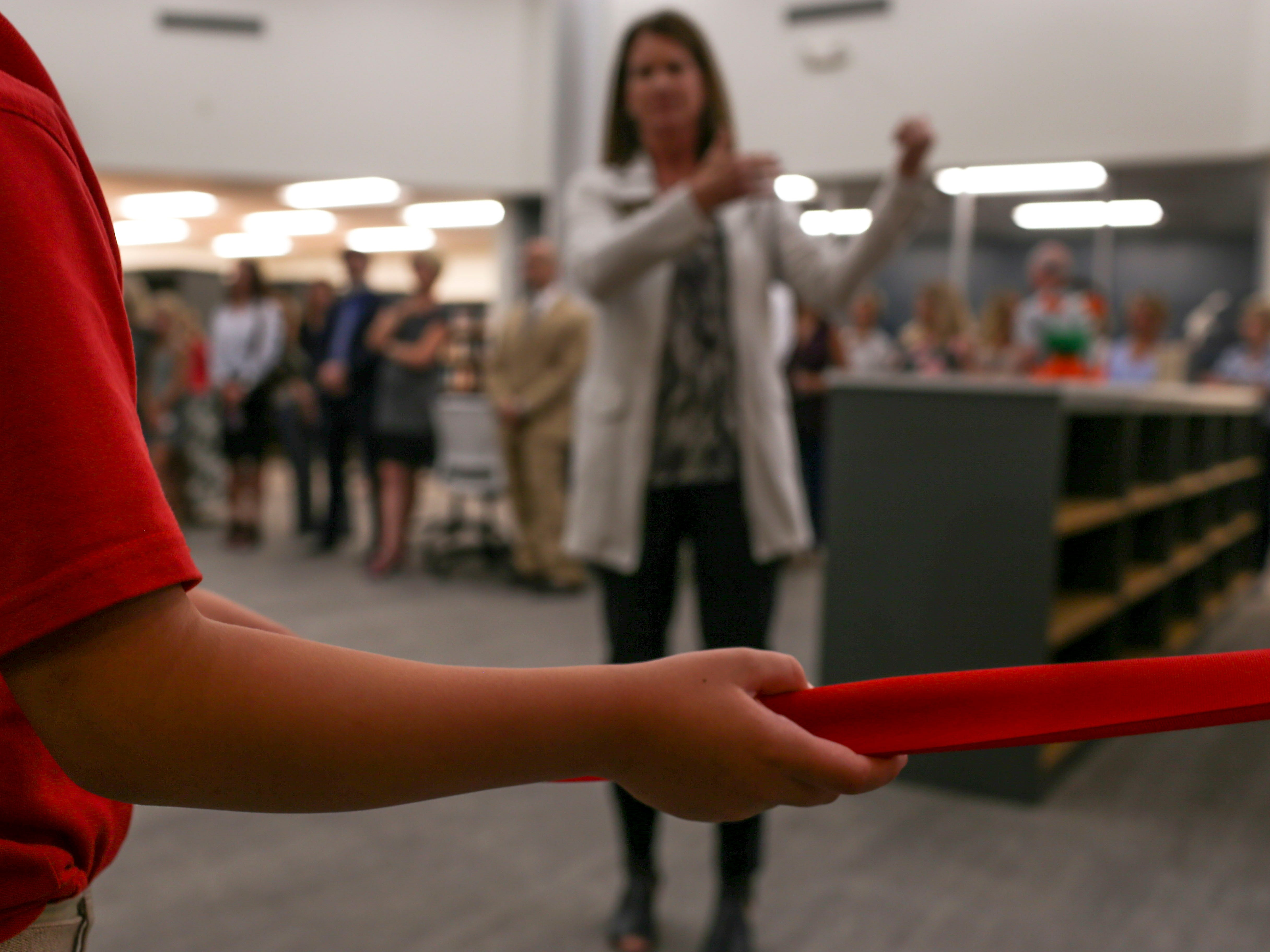 Patrick Campbell, 9, stretches out a red ribbon that will be cut to mark the opening of a new library at University School of Jackson in Jackson, Tenn., on Monday, Aug. 20, 2018.