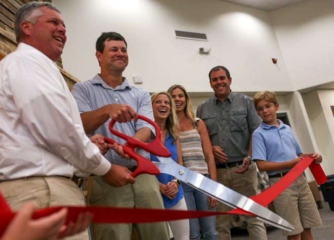 Nick Campbell, center, holds back laughter while those surrounding him chuckle after the large scissors fail to cut a red ribbon rolled out for the opening of a new library at University School of Jackson in Jackson, Tenn., on Monday, Aug. 20, 2018.