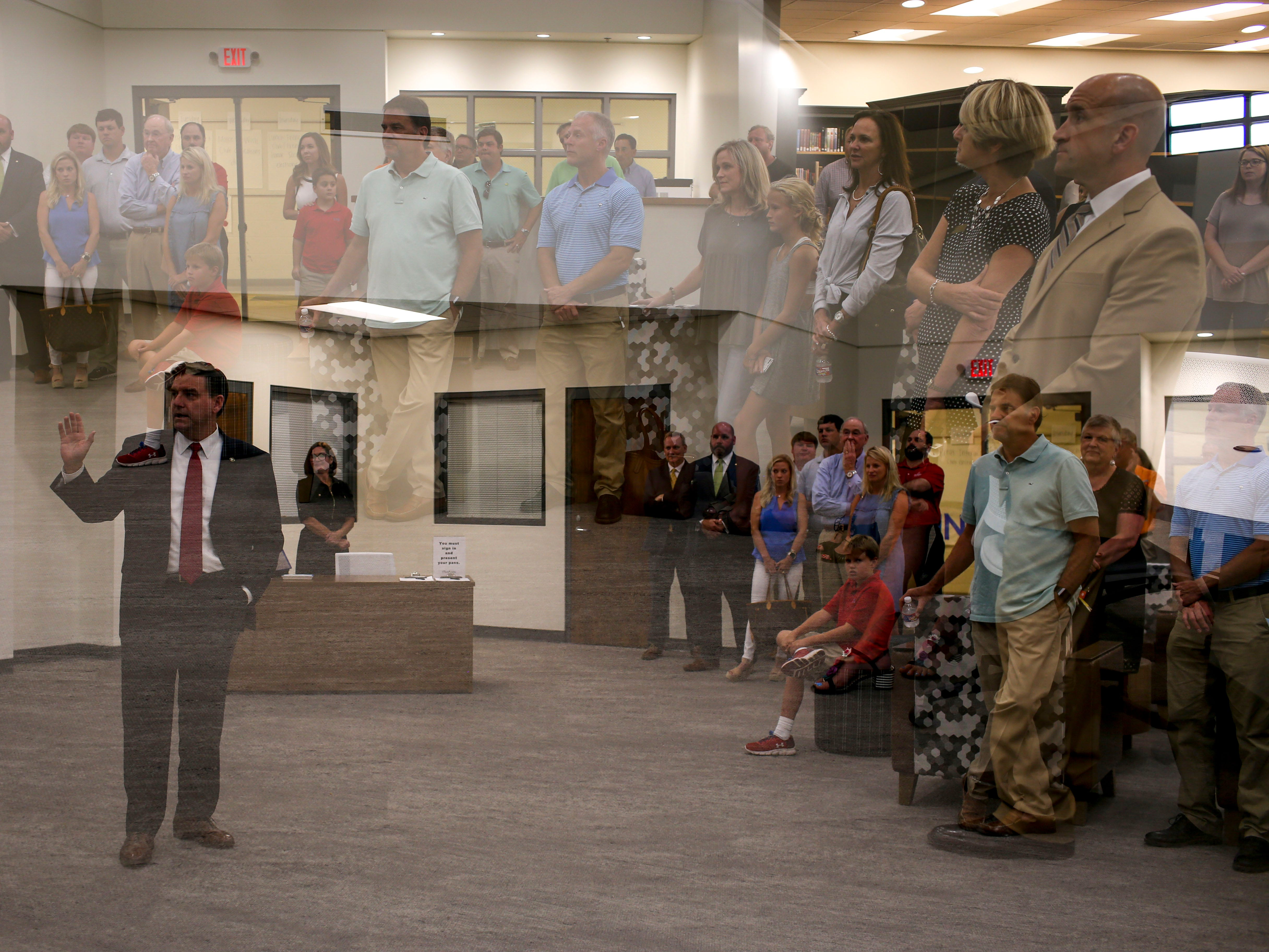 In this double exposure, Stuart Hirstein, left, speaks to parents about the new library at University School of Jackson in Jackson, Tenn., on Monday, Aug. 20, 2018.