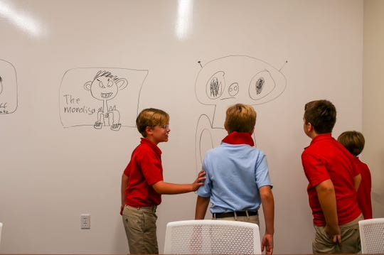 (From left to right) Patrick Campbell, 9, Jake Campbell, 10, Jack Crider, 9, and Landon McCord, 8, step back and examine their work drawing aliens on the walls of a room at University School of Jackson in Jackson, Tenn., on Monday, Aug. 20, 2018.