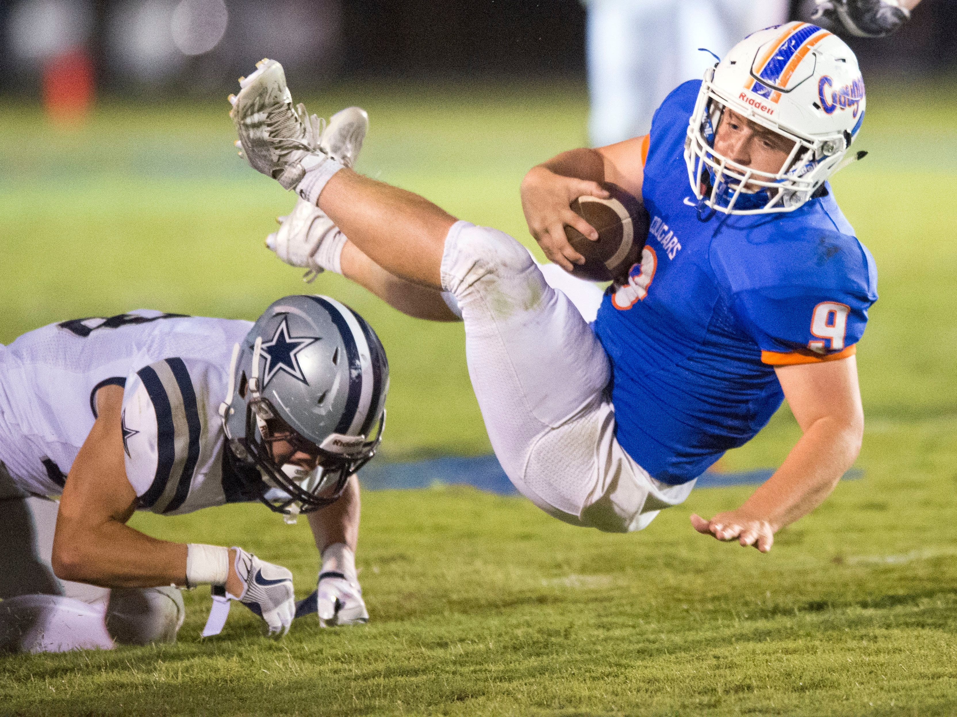 Campbell County's Patrick Strunk is tripped up by Farragut's Braden Collins, left, at Campbell County High School on Thursday, September 29, 2016.