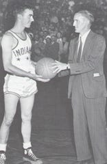 Indiana's Phil Buck of Rossville receives the game ball from Harold Harrison, sports editor of The Indianapolis Star, after the 1947 Indiana-Kentucky All-Star game.