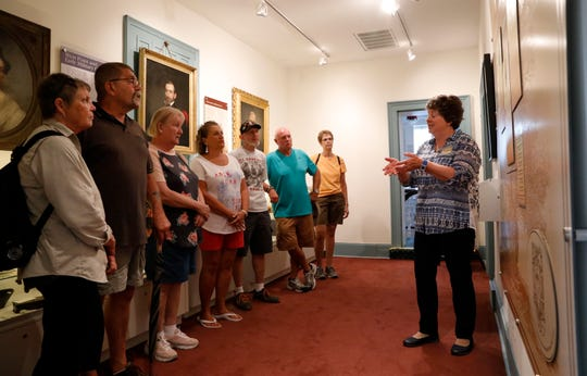Karen Wagner, a volunteer with the Fairfield County Heritage Association, leads a group of Vietnam Veterans and their spouses through the Sherman House Tuesday morning, Aug. 21, 2018, in Lancaster. The group served together in Vietnam have met once a year for the past 15 years at different locations throughout the country.