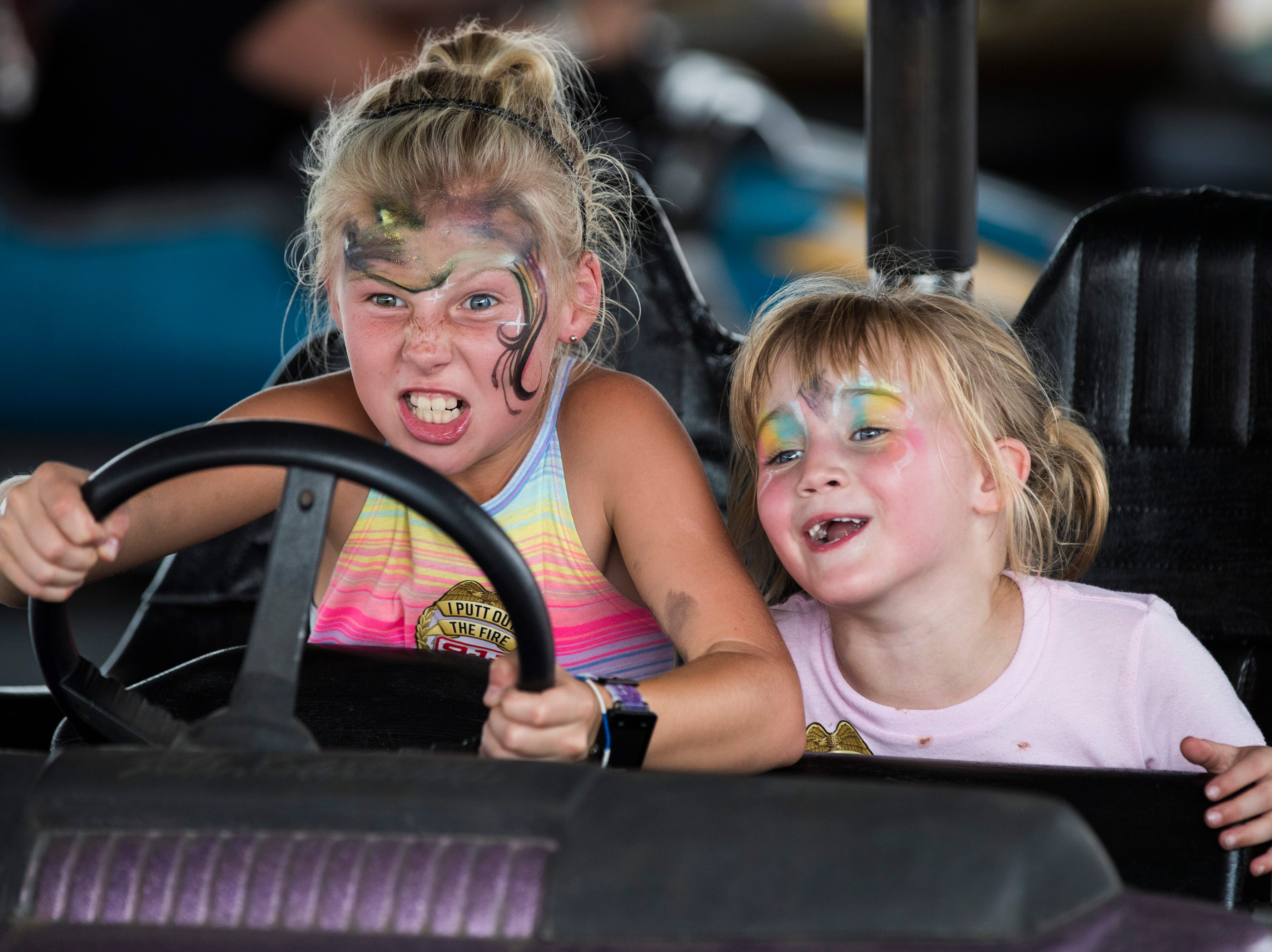 Riley James, 9, left, shows no fear as co-pilot Lilly Cash, 6, looks on during a ride in a bumper car at the Kentucky State Fair on Monday. Aug. 20, 2018