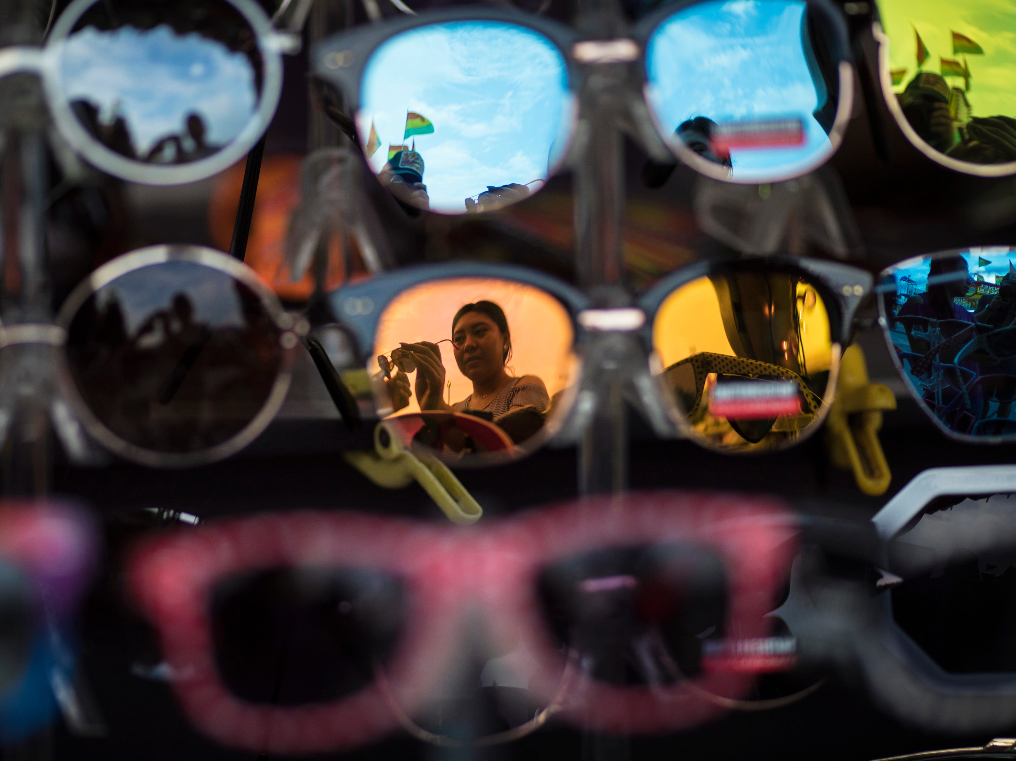 A woman tries on sunglasses for sale at the Kentucky State Fair on Monday. Aug. 20, 2018