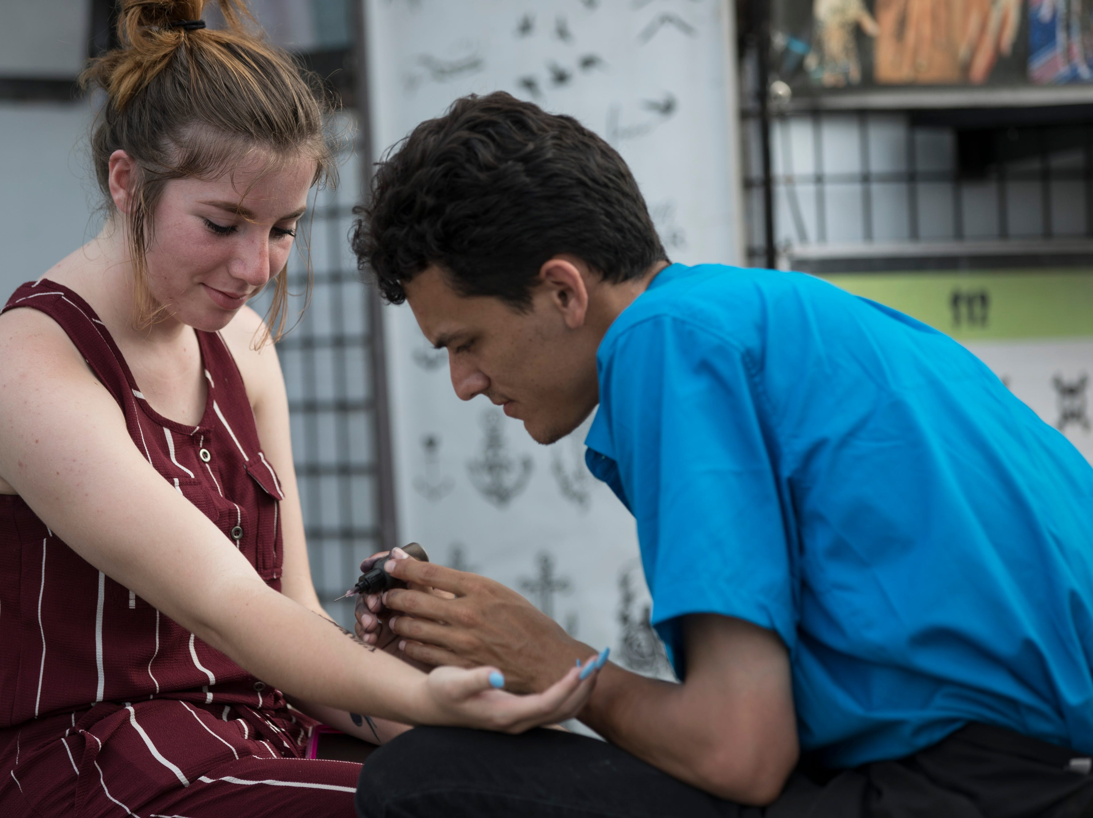 Billie-Rae Allport gets a fake tattoo by Christian Torres at the Kentucky State Fair on Monday. Aug. 20, 2018