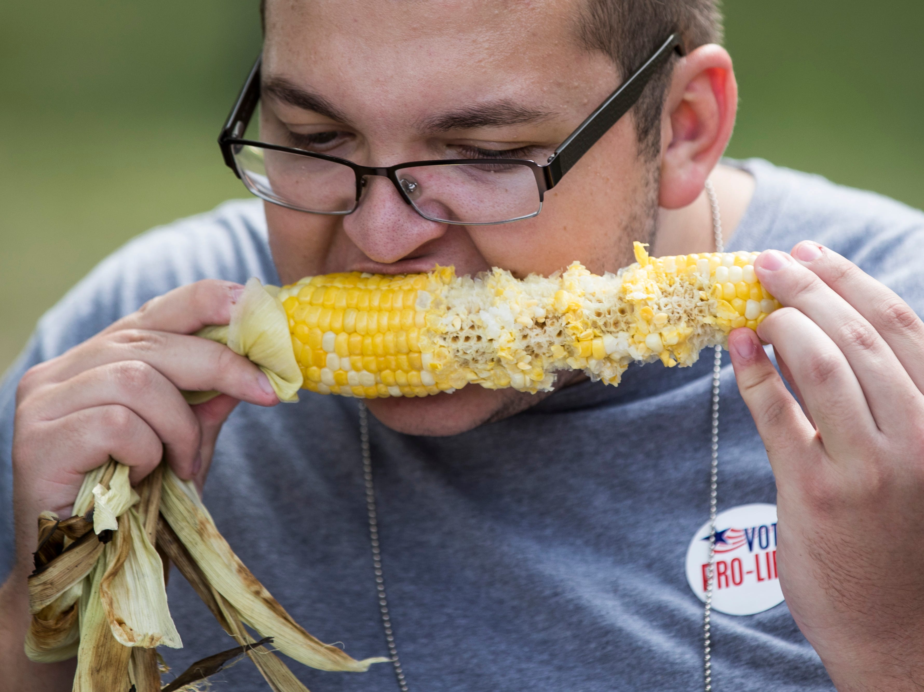 Jared Stoner tries out some corn on the cob at the Kentucky State Fair on Monday. Aug. 20, 2018