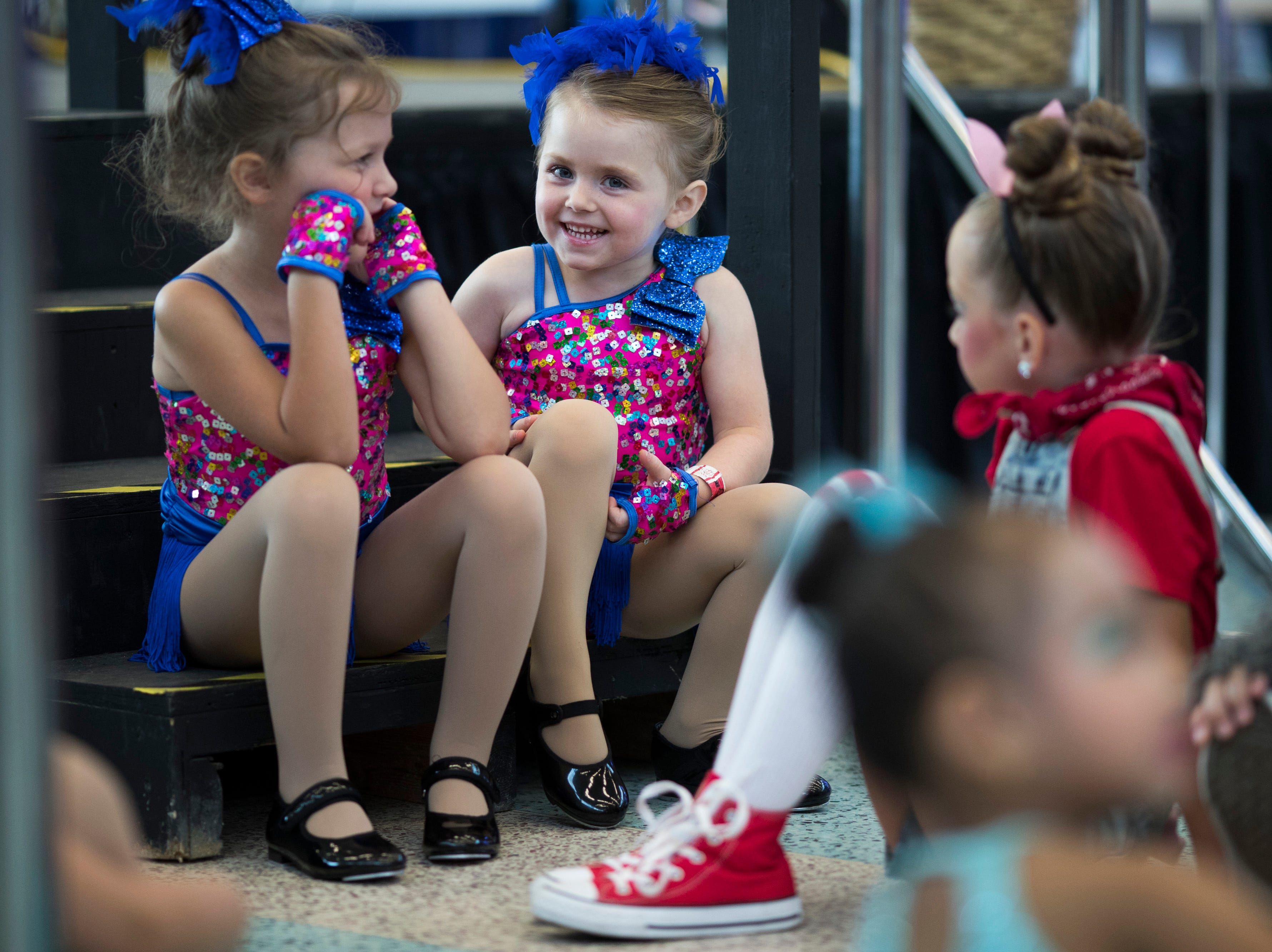 Kate Osborne, left, and Grace Coyle sit backstage before a dance performance at the Kentucky State Fair on Monday. Aug. 20, 2018