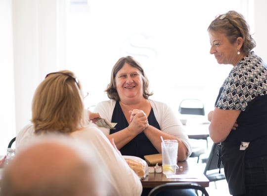 "Lori Conarton, right, chats with customers Tuesday, Aug. 21, 2018, at her newly-opened MorningLory Cafe & Bakery in downtown Dimondale.  Maryann Hunt, middle, worked at the restaurant when it was Mike's Village Restaurant, and Debby Conklin, left, says her son worked there in the 80's.  ""The community is finally back together again,"" Conklin said."