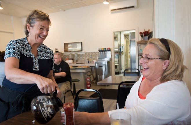 "MorningLory Cafe & Bakery owner Lori Conarton, left, refills Debby Conklin's coffee Tuesday, morning,  Aug. 21, 2018, at MorningLory Cafe & Bakery in downtown Dimondale.  Conarton had to close her neighborhood eatery from July 31st through Aug. 14 after one of her employees tested positive for COVID-19.  ""Operating at 50% capacity is a challenge, but we have a loyal following and we'll get through this."""