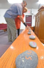 Brian and Bridgette Olar look at rocks with the names of children to be prayed for on the alter at Belmont Community Church