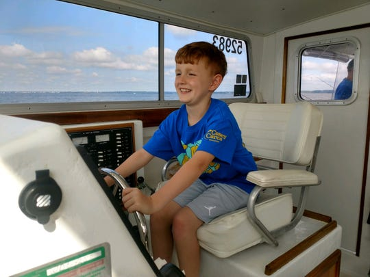 Liam Young steers a charter boat during a recent fishing trip to Chesapeake Bay provided by the Casey Cares Foundation.