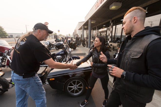 Harley Owners Group regional manager Paul Raap (left) greets Holly and Cody Tupper before the start of their ride to Milwaukee Aug. 21 at Destination Harley-Davidson in Tacoma, Wash. The Tuppers, of Victoria, British Columbia, are making their last big ride before starting a family.