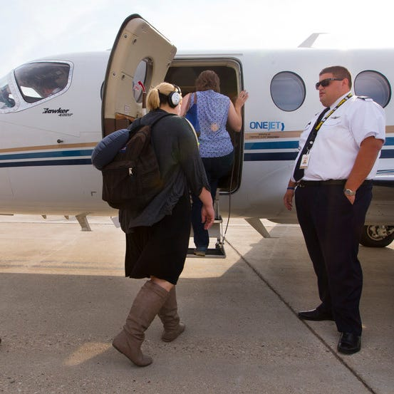 Pilot Adam Danenberg (right) greets passengers boarding a OneJet flight to Pittsburgh at Mitchell International Airport last October. OneJet has apparently stopped serving Milwaukee.