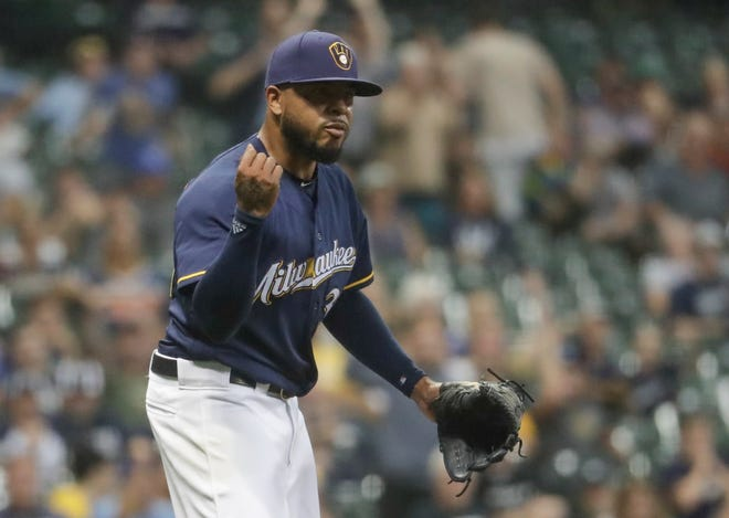 Jeremy Jeffress reacts after the Brewers turn a double play against the Reds to close out the game on Monday night at Miller Park.