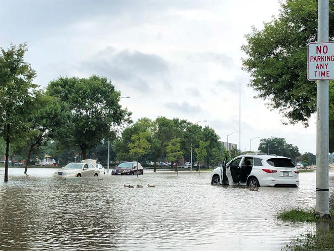 Ducks swim on flooded Mineral Point Road at Gammon Road near abandoned cars on Madison's west side. More than a foot of rain fell on Madison Monday, flooding many areas of the city's west and far west side.