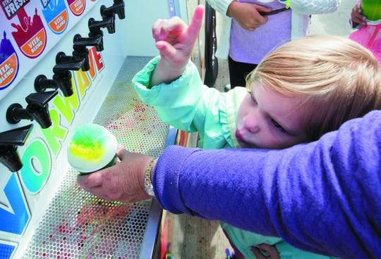 Emma Claire Koper instructs her mother on which flavors to add to her snow cone during a past Oconomowoc Fall Festival.
