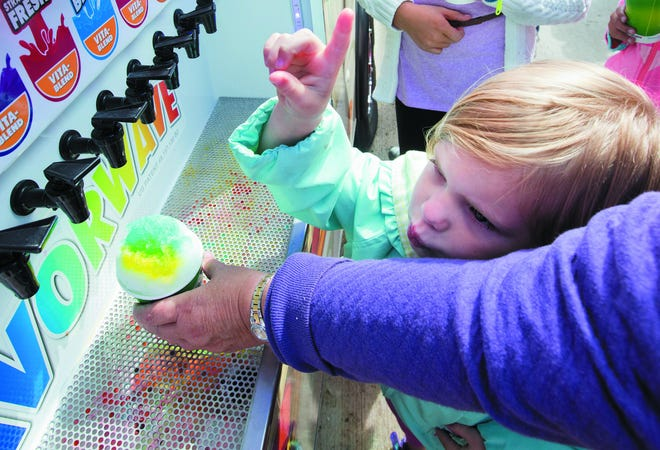 Emma Claire Koper instructs her mother on which flavors to add to her snow cone during a past Oconomowoc Fall Festival. This year's festival is Sept. 8 in downtown Oconomowoc.
