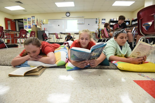 Norfork Elementary School sixth graders, from left, Emma Richard, Kaylynn Chapman and Arinne Woody take advantage of flexible seating during a reading session Tuesday at the school. Allowing students to be comfortable while learning may well be another factor in the district's recent testing performance.