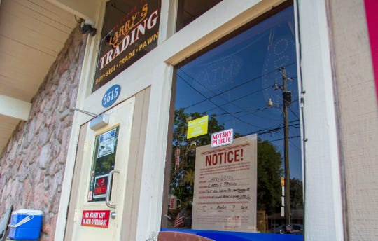 A public notice hangs in the window at Larry's Trading announcing a public hearing on a proposed liquor license application.