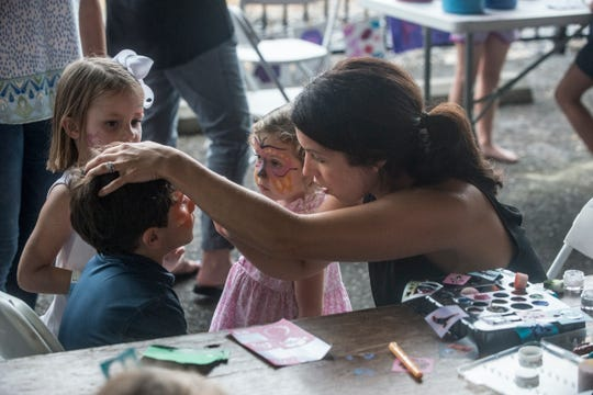 Children get their faces painted in the kids area. Hog Days of Summer returned for its second year at the Union Station Train Shed in Montgomery on Saturday, Aug. 18, 2018.