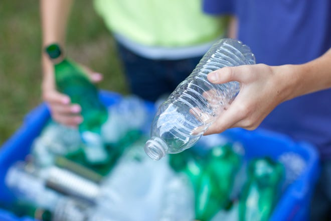 Putting clear and green bottles and metal cans in recycling blue bin outside in yard