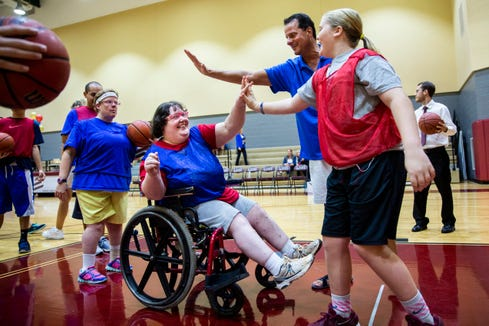 Ashton Taylor, from right, and Lou Georgelos high five Stevi Fye after she made a basket during warm-ups before an all-star basketball game featuring the junior high girls team and the STARability Foundation team at First Baptist Academy in Naples on Friday, August 17, 2018.