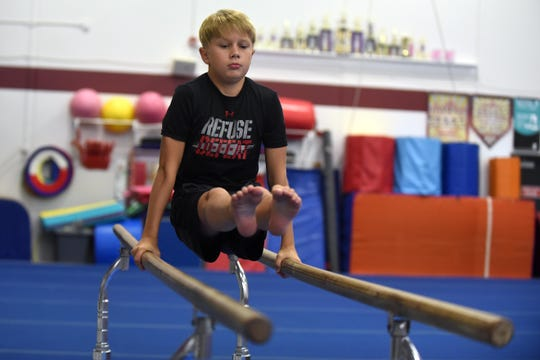 Ethan Baker, 11, practices on the bars at the Licking County Family YMCA's Mitchell Center. Baker won the Level 4 boys division at the YMCA National Championship earlier this summer.