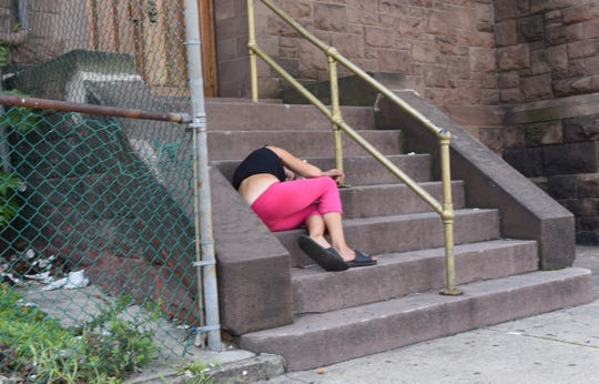 An unidentified woman takes a nap on the stairs at United Presbyterian Church on Van Houten Street in Paterson. The area is known as a frequent location for streetwalkers to meet prospective customers.