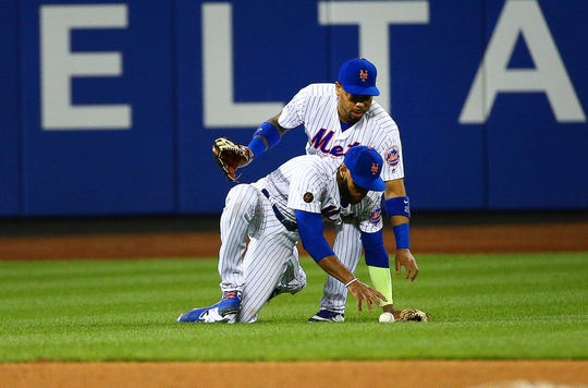 New York Mets shortstop Amed Rosario (1) and left fielder Dominic Smith (22) collide and drop a fly ball for a run against the San Francisco Giants during the 13th inning.