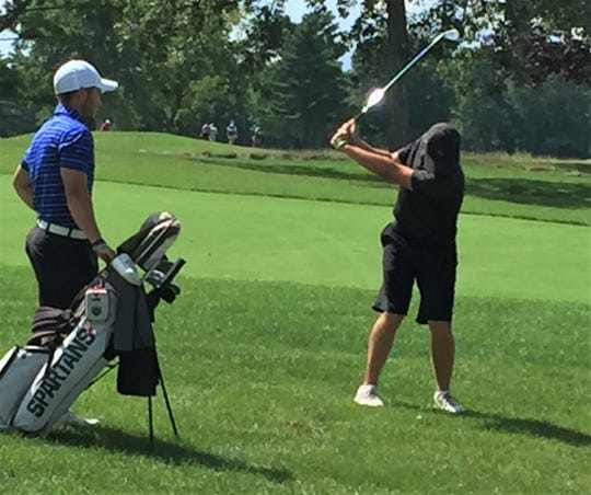 GAM champion James Piot (right) takes aim on the 18th fairway with his caddy Josh Stein.