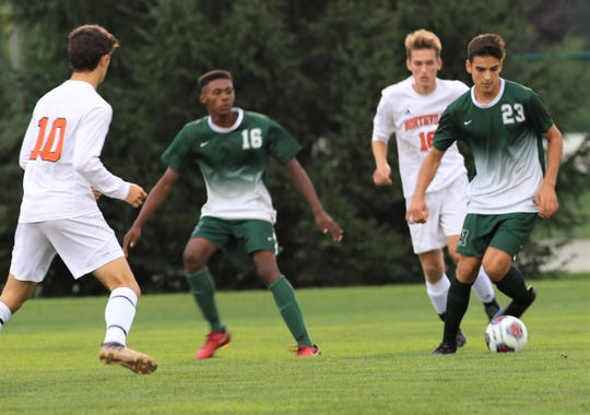 Novi's Gonzalo Sanz Cristobal (23) looks for an opening against Nortville's Demetri Zervos (10).