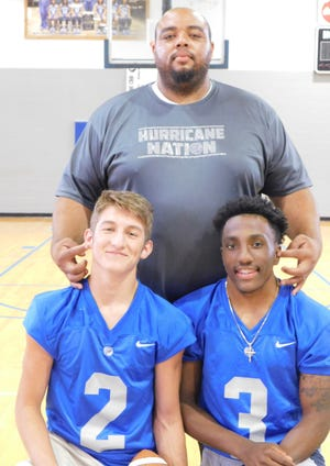 North Central head football coach Jacobi Thierry and seniors Jacob Hawkins (2) and Dymantae Nevills (3) pose during Monday's team photo day.