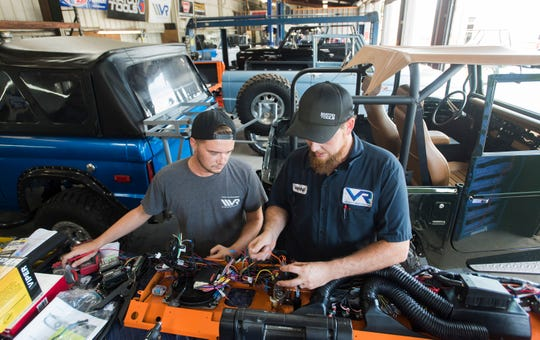 Josh Lucas and Marshall Cantrill assemble an electronic dashboard cluster for a Bronco build at Velocity Restorations in Warrington on Tuesday, Aug. 21, 2018. Velocity Restorations is a Pensacola-based automotive company that specializes in restoring the classic Ford truck to new condition.