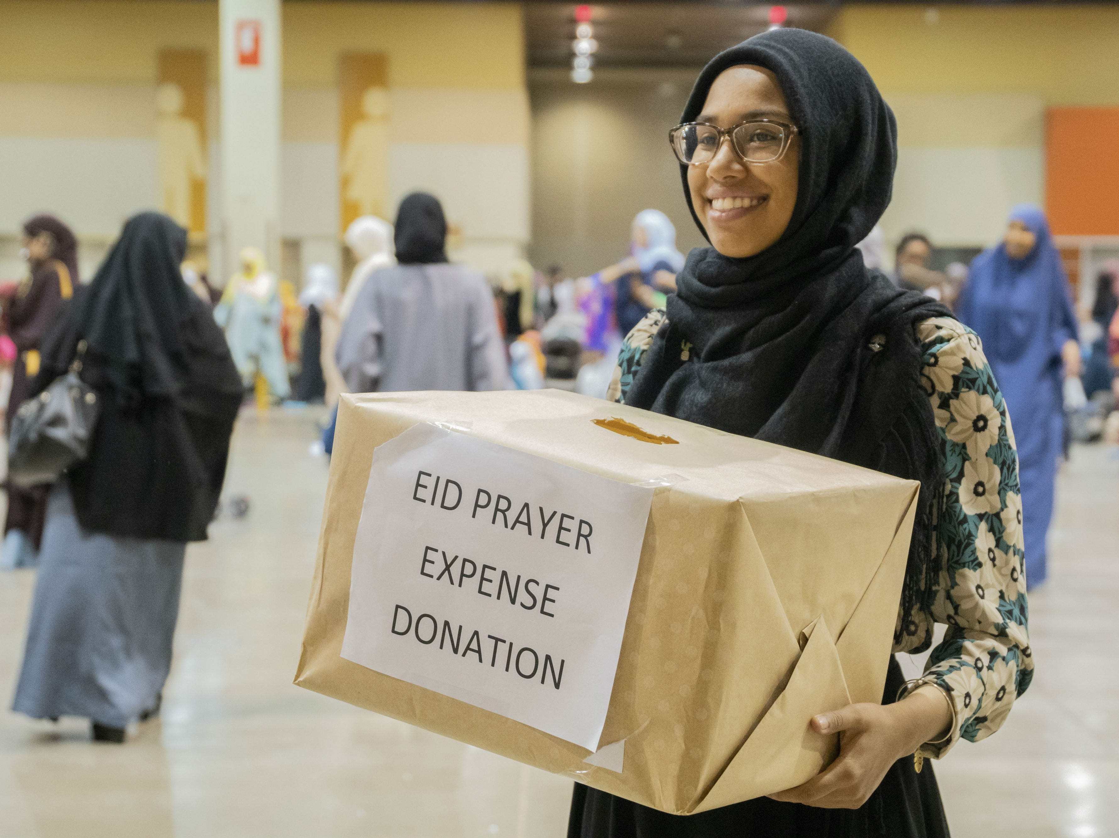 A young woman greets worshippers with a donation box on Aug. 21, 2018, in Phoenix.