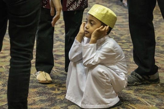 A boy sits while his parents socialize at an Eid celebration on Aug. 21, 2018, in Phoenix.